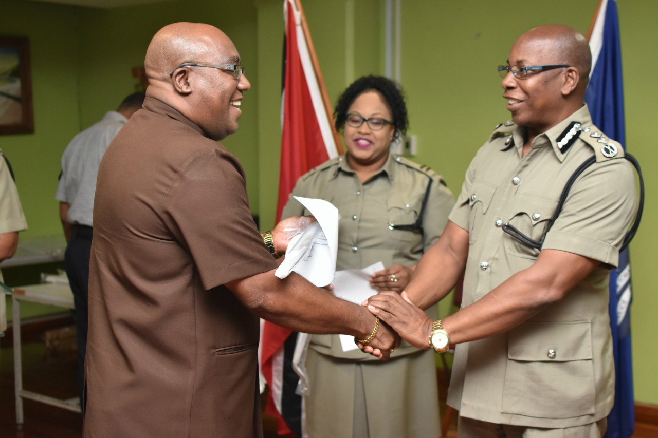 Acting Commissioner of Police Stephen Williams presents Acting ACP Anthony Bucchan with a letter of appointment made posthumously for Inspector Kim Bucchan.