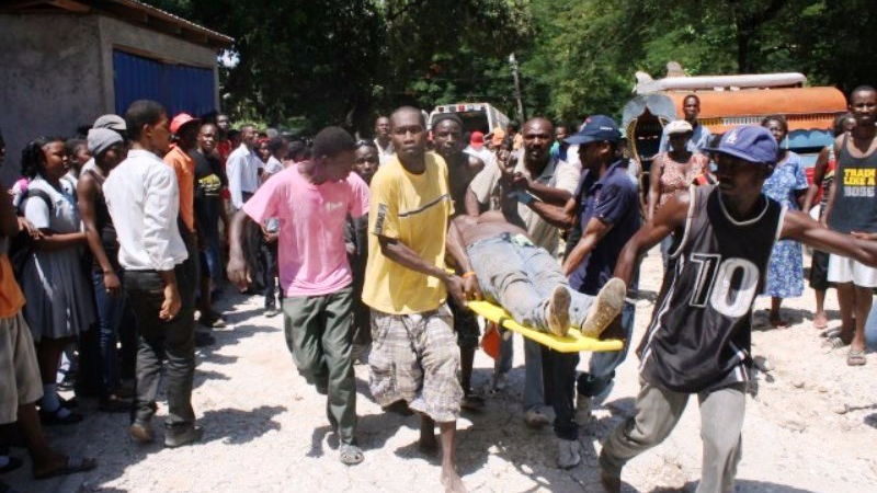 An injured person is carried from the scene of the bus crash in Southern Haiti