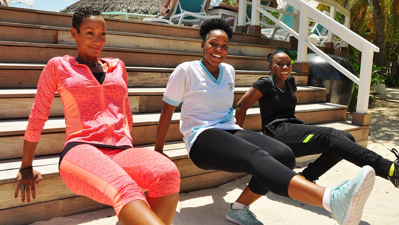 Smiling through the pain: Sandals Resorts' Group Fitness Manager, Melody Cargill (left) leads the class as Ophir Gayle (centre) and Shanique Cunningham try to keep up.