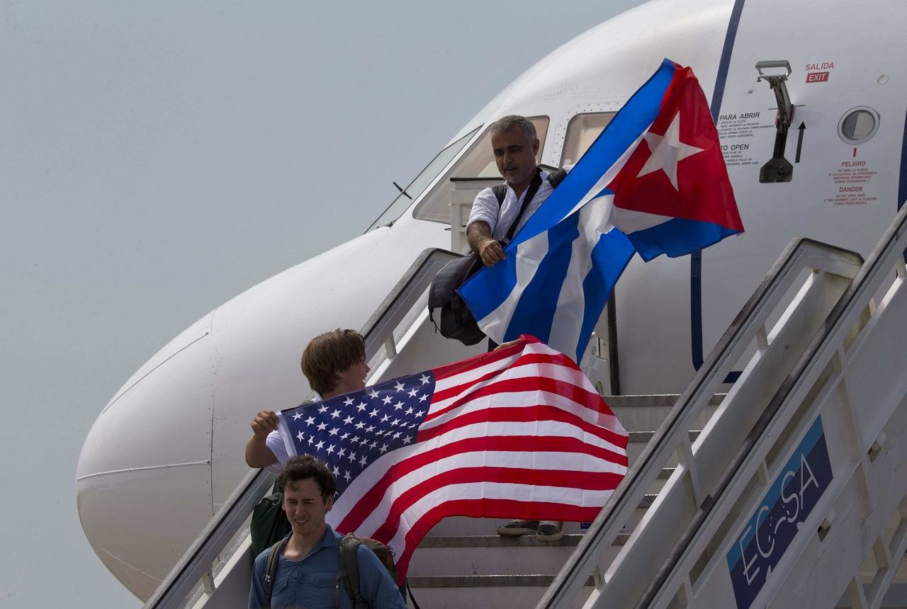 In this Aug. 31, 2016 file photo, two passengers deplane from JetBlue flight 387 waving a United States, and Cuban national flag, in Santa Clara.