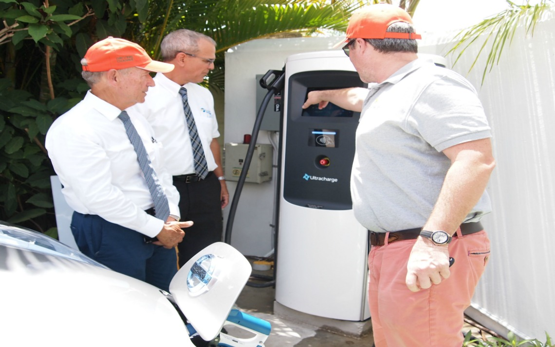 Managing Director of Megapower, Simon Richards demonstrating to Realtor, Sir Paul Altman (far left) and Managing Director of Emera, Peter Williams how the electrical charger port is used.