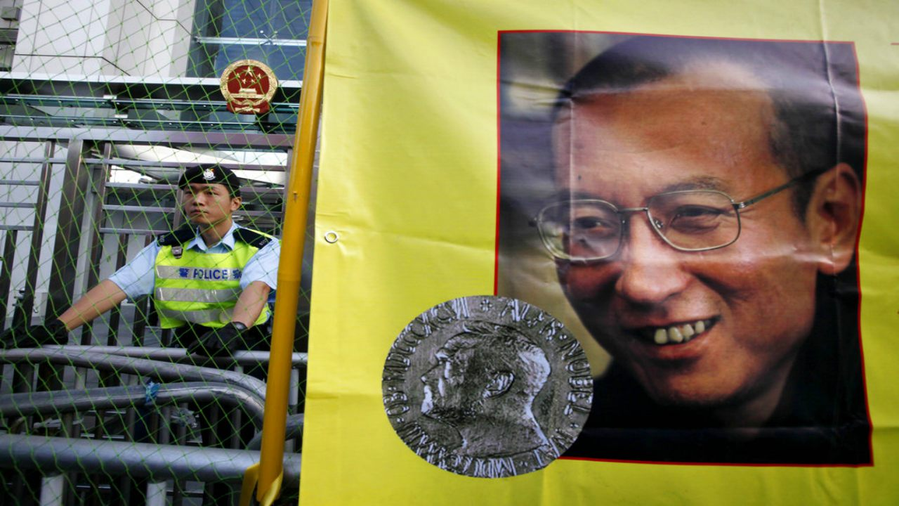 In this Dec. 5, 2010 file photo, a police officer stands guard beside a picture of jailed Chinese dissident Liu Xiaobo outside the Chinese government liaison office in Hong Kong. Jailed Chinese Nobel peace laureate Liu has been released on medical parole after being diagnosed with late-stage liver cancer, his lawyer said Monday, June 26, 2017. (AP Photo/Kin Cheung, File)