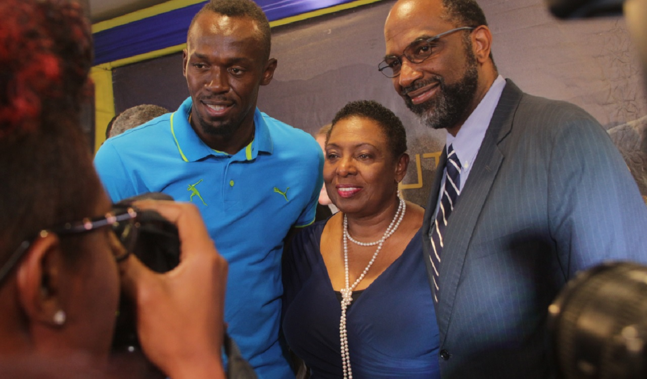 Legendary sprinter Usain Bolt (left) takes time out to pose for a photo with Sports Minister Olivia Grange (centre) and Earl Jarrett (right), General Manager of  Jamaica National (JN) Group on Thursday at the Jamaica Pegasus Hotel.  Occasion was a press conference to introduce the top athletes for Saturday's  JN Racers Grand Prix at the National Stadium.