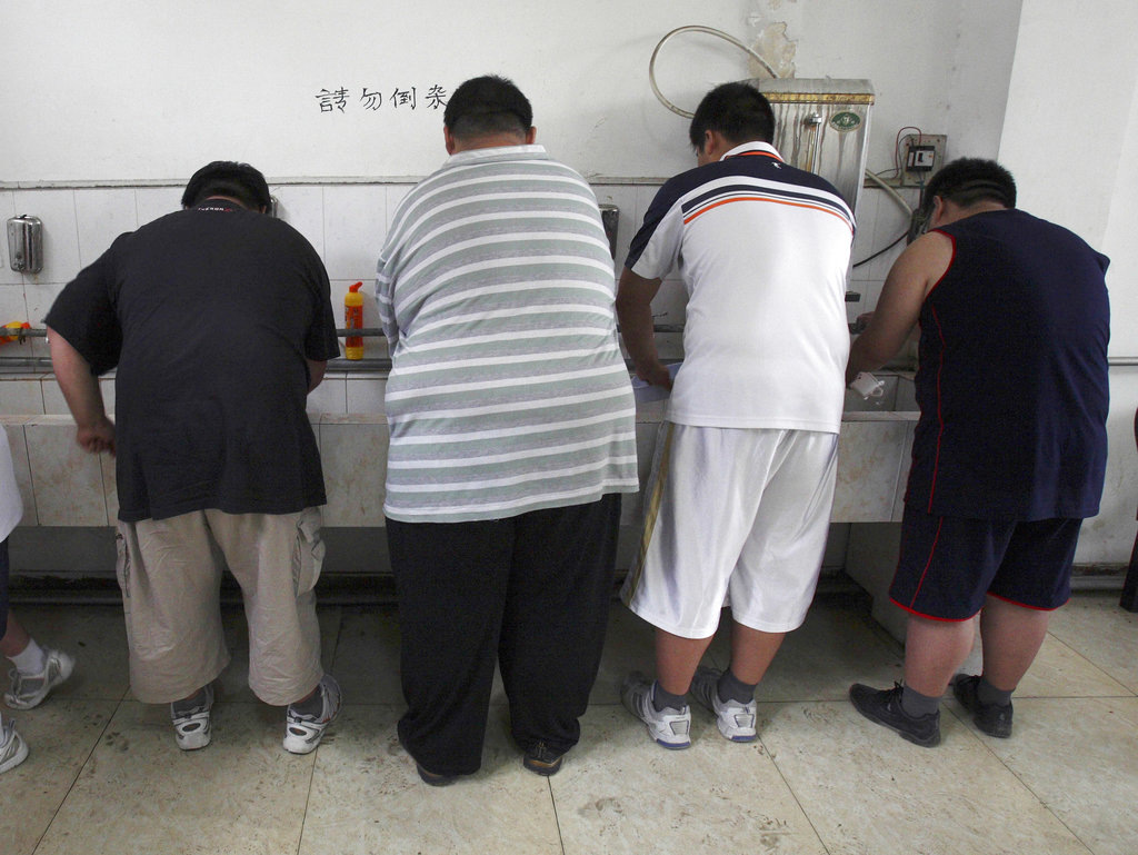 In this Thursday, July 24, 2008 file photo, obese patients wash their plates after lunch at the Aimin Fat Reduction Hospital in Tianjin, China. The hospital uses a combination of diet, exercise and traditional Chinese acupuncture to treat rising obesity rates. Research released Monday, June 12, 2017 found the obesity epidemic is getting worse in most parts of the world, according to data between 1980 and 2015. (AP Photo/Ng Han Guan)