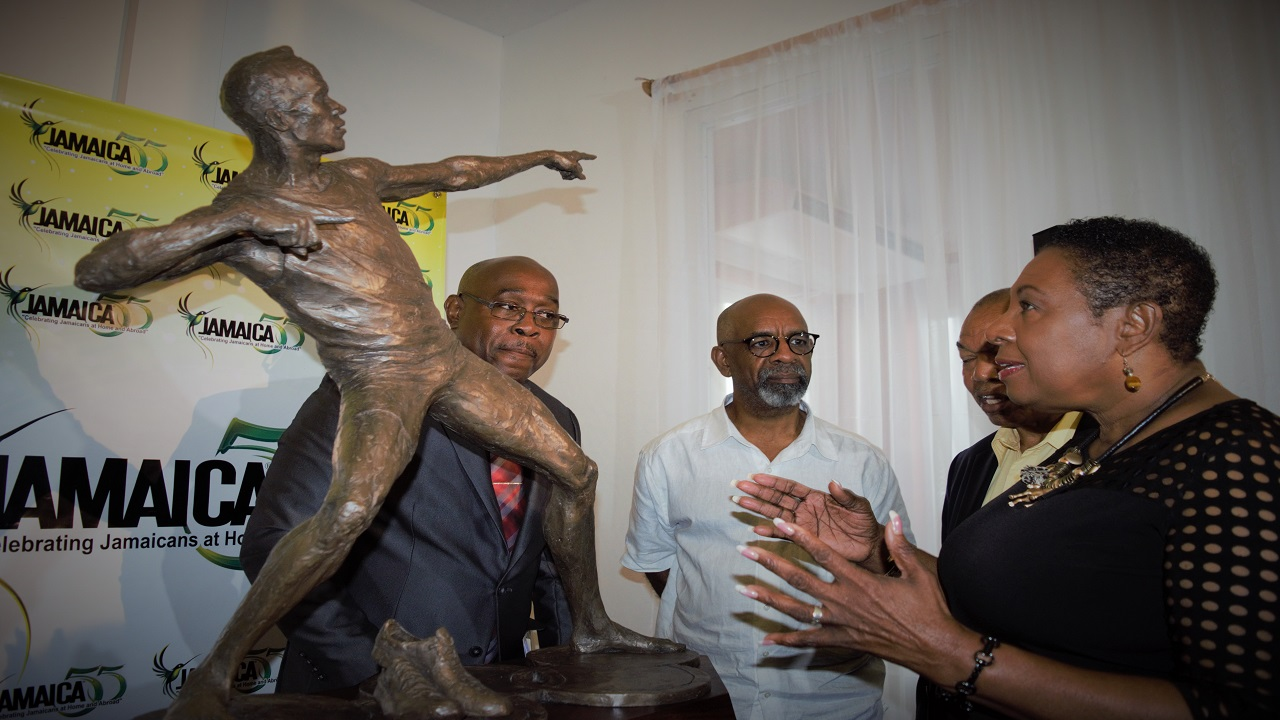 Minister of Culture, Gender, Entertainment and Sport, Olivia Grange expresses how pleased she is with the maquette of the Usain Bolt Statue which was unveiled Friday. Also pictured (from left) are Ian Forbes, Board Director of the Sport Development Foundation; Sculptor Basil Watson and President of the JAAA, Dr Warren Blake (partially hidden).