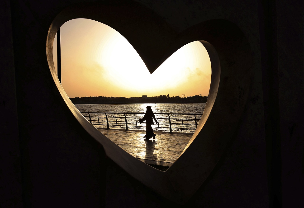 In this May 11, 2014 file photo, a Saudi woman seen through a heart-shaped statue walks along an inlet of the Red Sea in Jiddah, Saudi Arabia. A young Saudi woman has sparked a sensation online by posting a video of herself in a miniskirt and crop top walking around in public, with some Saudis calling for her arrest and others rushing to her defense.