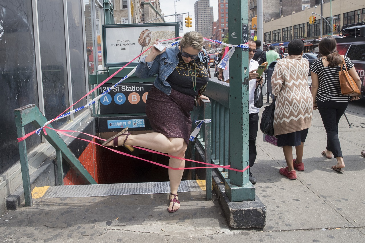 A commuter exits a closed off station after a subway train derailment, Tuesday, June 27, 2017, in the Harlem neighbourhood of New York.