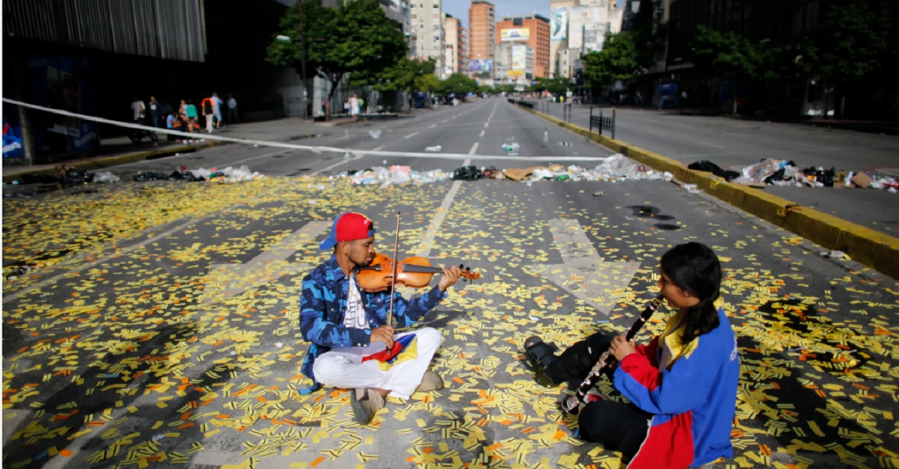 Musicians play their instruments as they sit in the middle of a road littered with metro tickets at a roadblock set up by anti-government protesters in Caracas, Venezuela, Thursday, July 20, 2017. Venezuelan President Nicolas Maduro and his opponents face a crucial showdown Thursday as the country's opposition calls a 24-hour national strike.