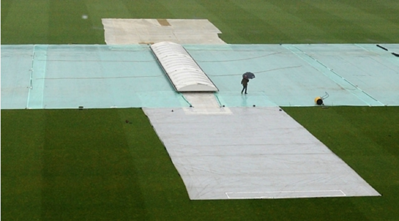 Rain forces covers onto the field in cricket.