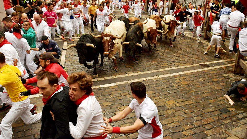 Revellers run in front of Fuente Ymbro's fighting bulls during the running of the bulls at the San Fermin Festival, in Pamplona, northern Spain, Monday, July 10, 2017.