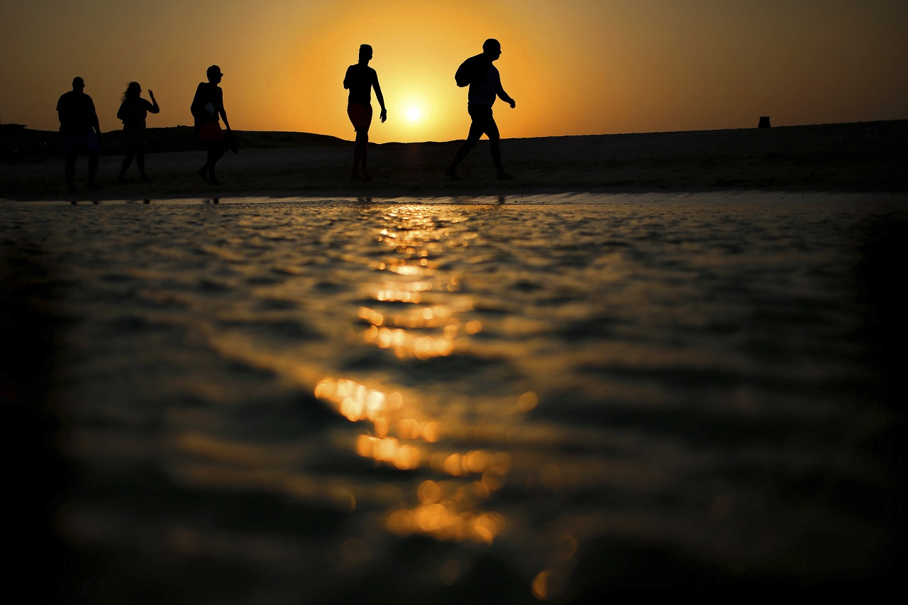 In this file picture taken Thursday, Aug. 20, 2015, tourists walk on the Giftun Island beach as the sun sets over the Red Sea in Hurghada, Egypt. Egypt's Interior Ministry said Friday, July 14, 2017 six foreign tourists, of various nationalities, were wounded when a man attacked them with a knife in the Red Sea resort of Hurghada.