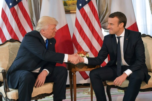 US President Donald Trump shakes hands with French President Emmanuel Macron.