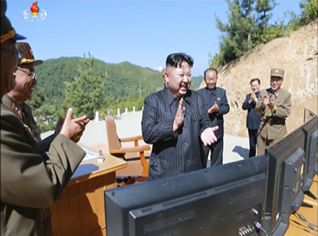 This image made from video of a news bulletin aired by North Korea's KRT on Tuesday, July 4, 2017, shows what was said to be North Korea leader Kim Jung Un, center, applauding after the launch of a Hwasong-14 intercontinental ballistic missile, ICBM, in North Korea's northwest.  (KRT via AP Video)