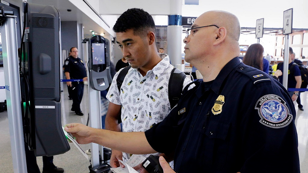 In a June 29, 2017, photo, U.S. Customs and Border Protection Officer Sanan Jackson, right, helps a passenger navigate the new face recognition kiosks at gate E7 for a United Airlines flight to Tokyo at Bush Intercontinental Airport in Houston.