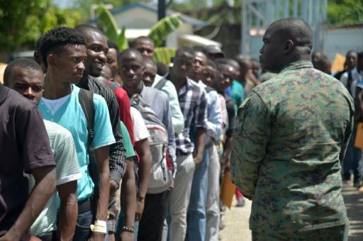 De jeunes postulants font la queue pour passer des entretiens de recrutement de soldats à Léogane, à l'ouest de Port-au-Prince, le 17 juillet 2017 / Photo : AFP / HECTOR RETAMAL