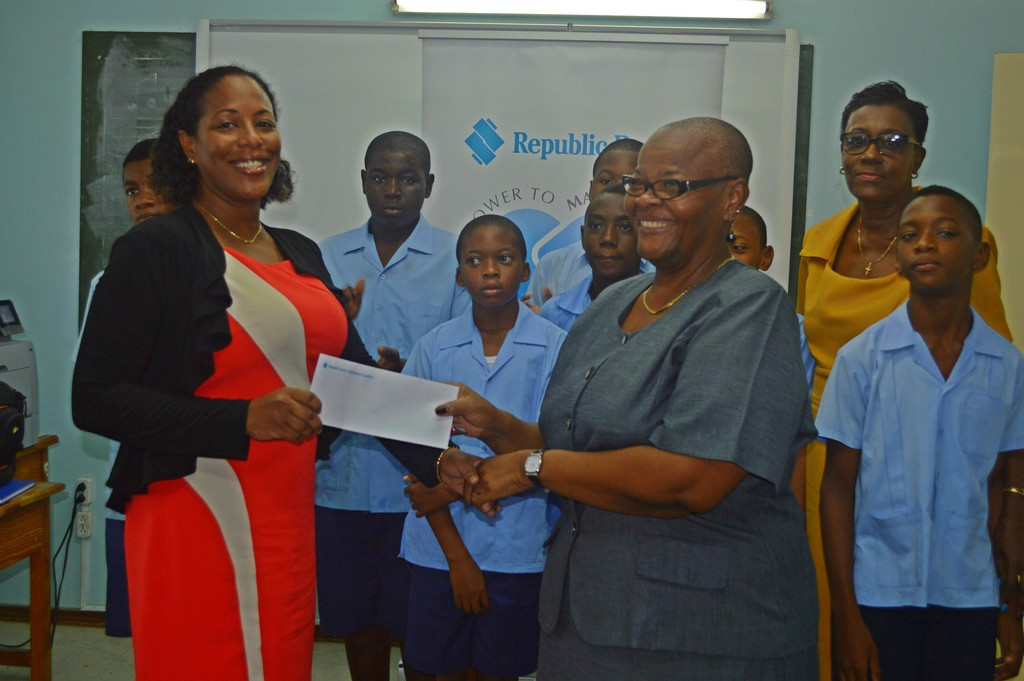 The principal of the Erdiston Special School, Cheryl Forde, accepts a donation from Michelle Pounder, Republic Bank's Senior Manager, Administration and Operations, witnessed by senior students of the school including Head Boy, Wesley Linton (right), and Senior Teacher Diana Murray.