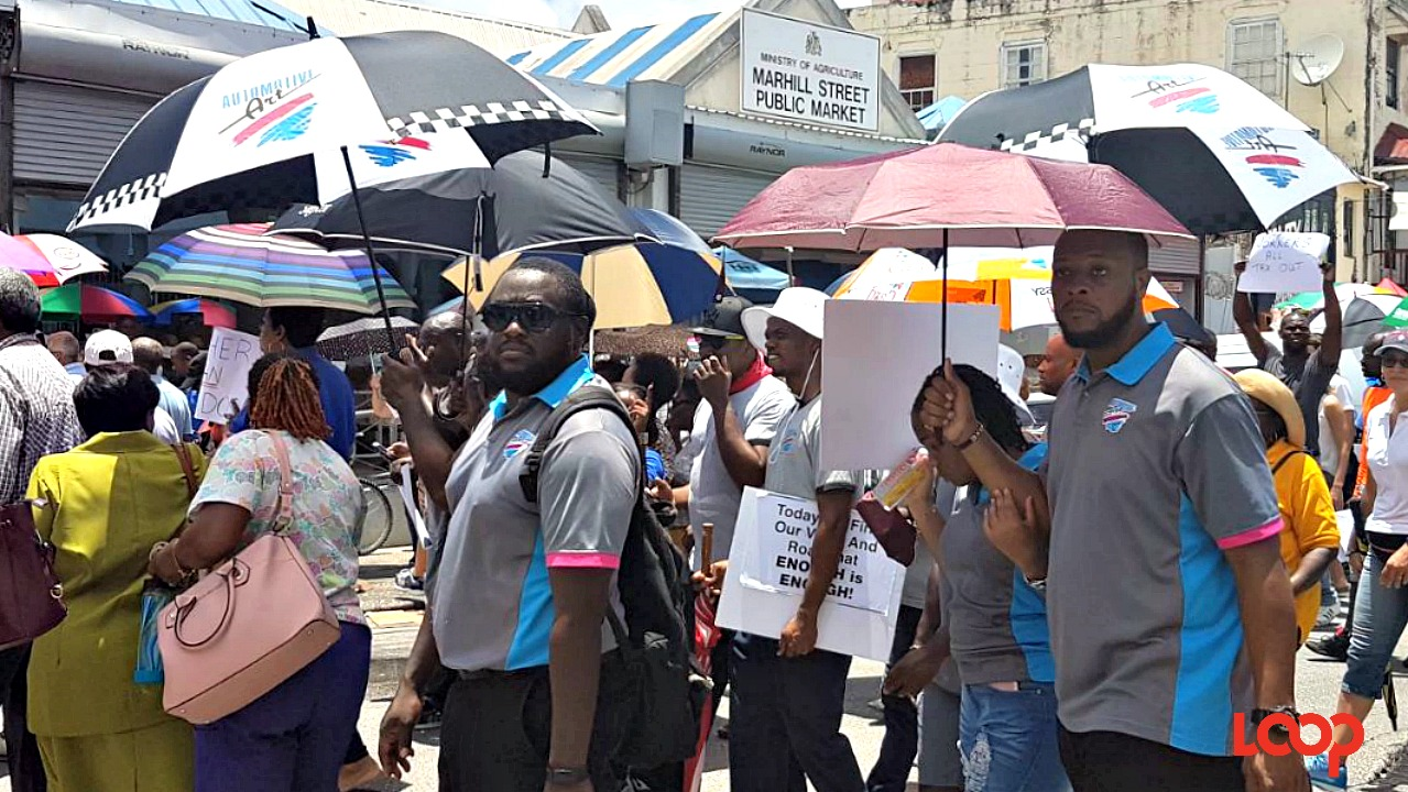 Employees dressed in company uniform during Monday's march through Bridgetown.