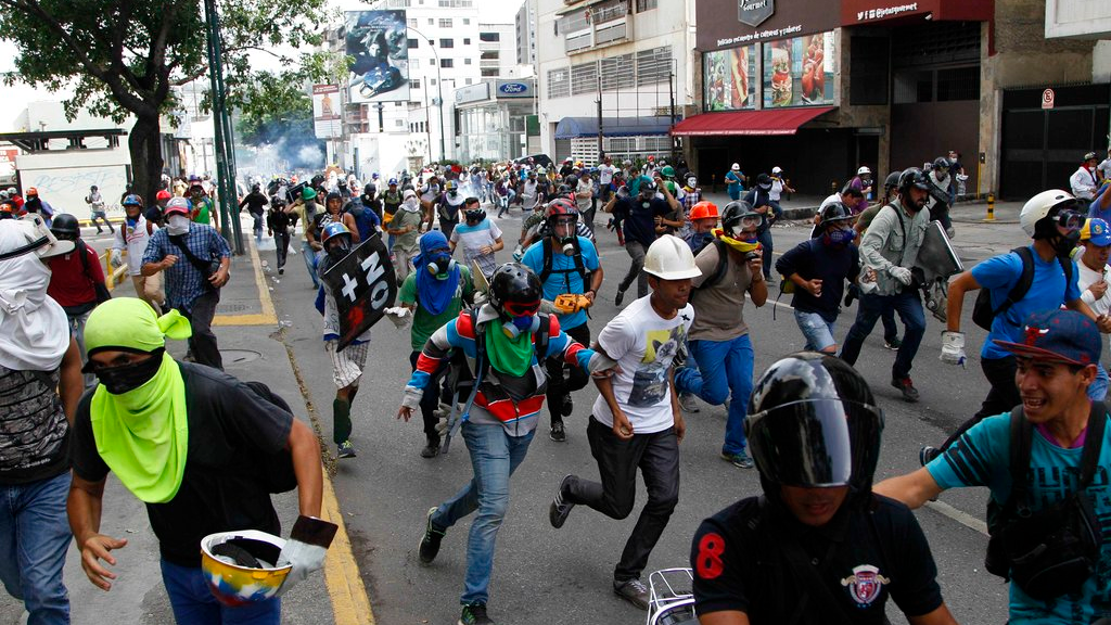 Anti-government demonstrators run away from security forces in Caracas, Venezuela, Wednesday, May 31, 2017. (AP Photo/Ariana Cubillos)