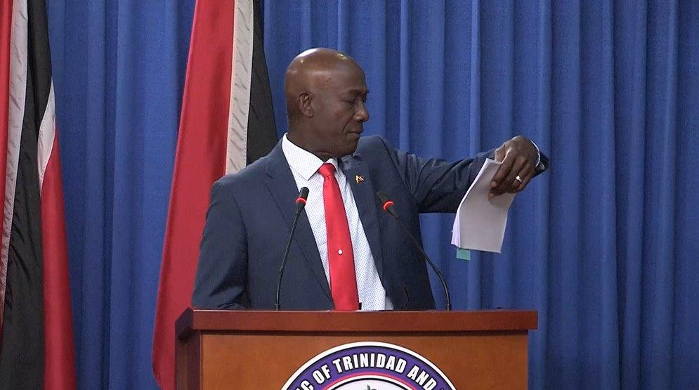 Prime Minister Dr Keith Rowley holds up the official valuation of Buccoo Estate (No Man's Land)