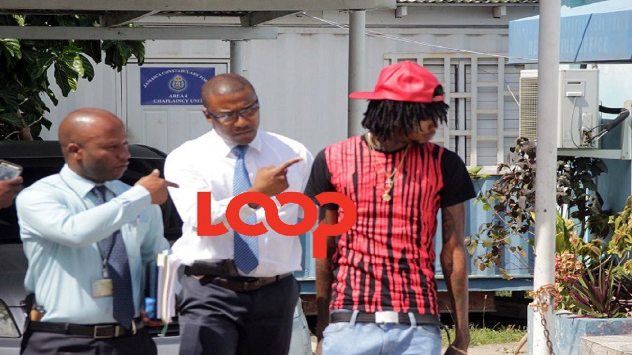 FILE - Alkaline (right) with detectives earlier this year after being questioned in relation to a criminal investigation in St Andrew, Jamaica. (Photo: Marlon Reid)
