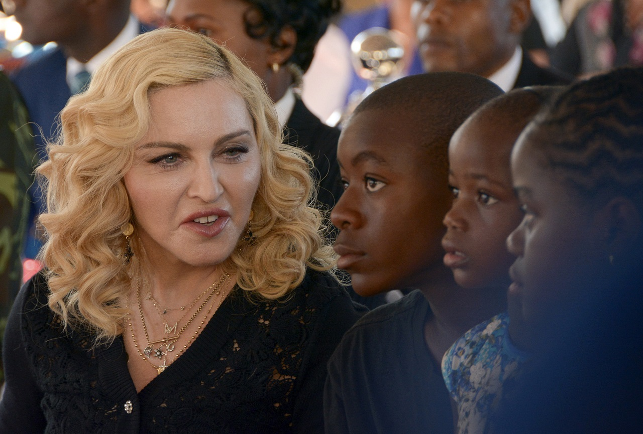 In this July 11, 2017 file photo, Madonna, left, sits with her adopted children David, Stella and Mercy, at the opening of The Mercy James Institute for Pediatric Surgery and Intensive Care, located at the Queen Elizabeth Central Hospital in the city of Blantyre, Malawi.