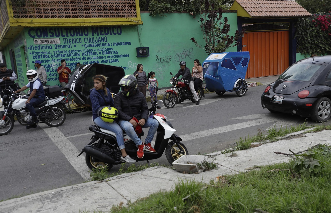 Residents and motorcycle taxi drivers stop to look at marines blocking the area where a suspected drug gang leader and seven others were killed in a shootout in the Tlahuac district of Mexico City, Thursday, July 20, 2017.