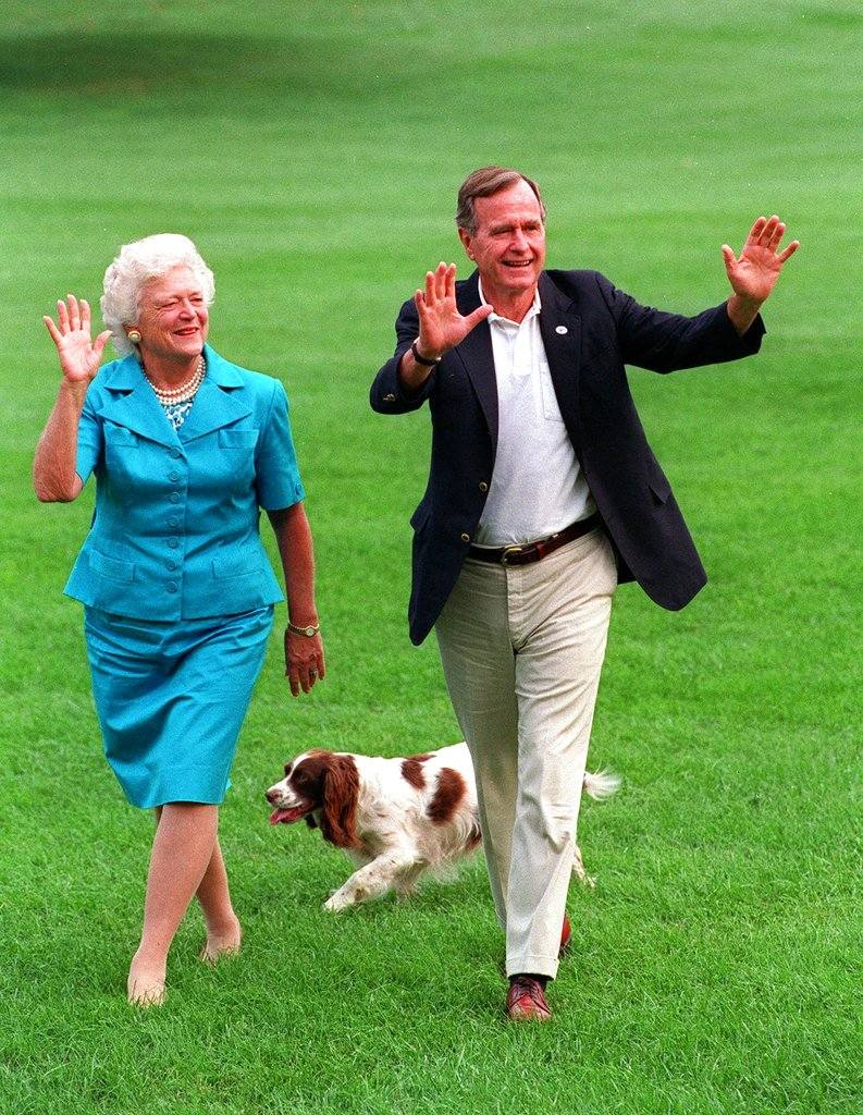 This Aug. 24, 1992 file photo shows President Bush, right, and first lady Barbara Bush walking with their dog Millie across the South Lawn as they return to the White House. (AP Photo/Scott Applewhite, File)