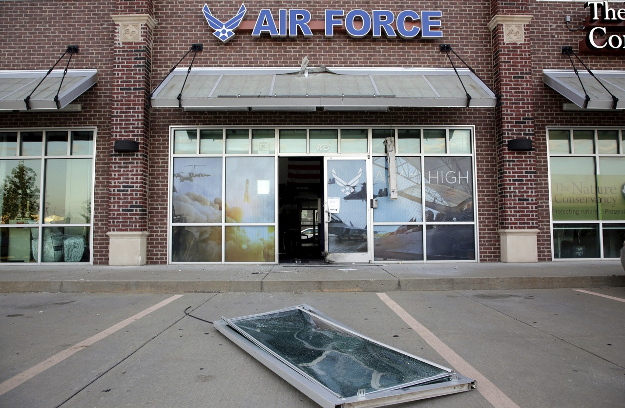 Glass and a door lie on the ground at the scene of an explosion at an Air Force recruiting office in Bixby, Okla., Tuesday, July 11, 2017, after an explosion Monday night outside an Air Force recruitment office.