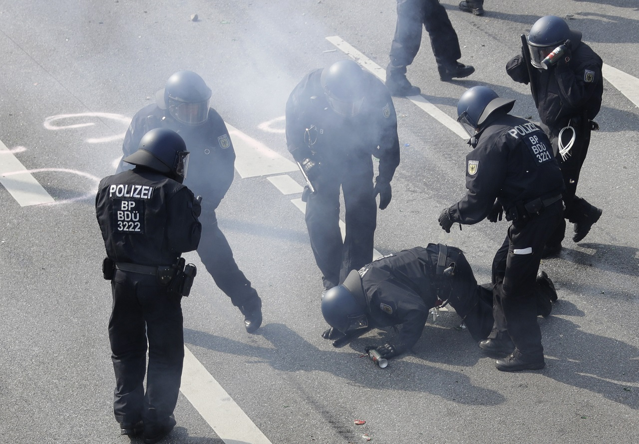 An injured police officer is attended by fellow officers during skirmishes with demonstrators on the first day of the G-20 summit in Hamburg, northern Germany, Friday, July 7, 2017. The leaders of the group of 20 meet July 7 and 8.