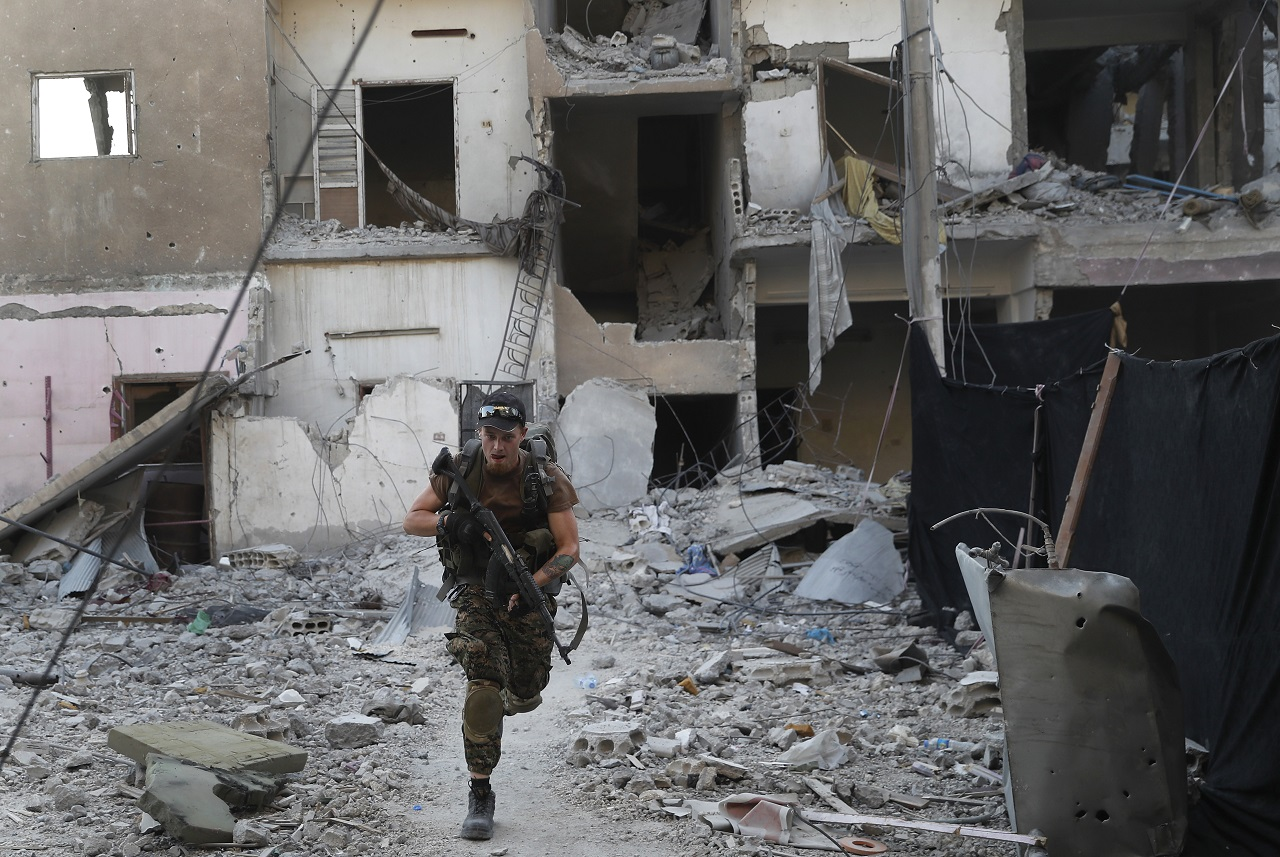 A U.S.-backed Syrian Democratic Forces fighter, runs in front of a damaged building as he crosses a street on the front line, in Raqqa city, northeast Syria, Thursday, July 27, 2017.