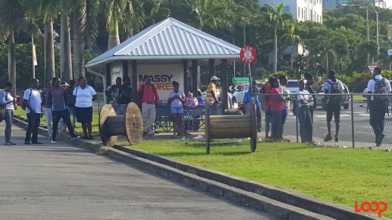 Commuters stranded at a bus stop in Warrens, St. Michael.