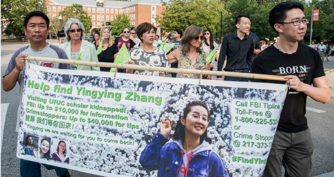Yingying Zhang's father Ronggao Zhang, left, and her friend Xiaolin Hou carry the banner as community members join together to walk for Yingying, a Chinese scholar who went missing three weeks ago, Thursday, June 29, 2017, in Urbana, Ill.