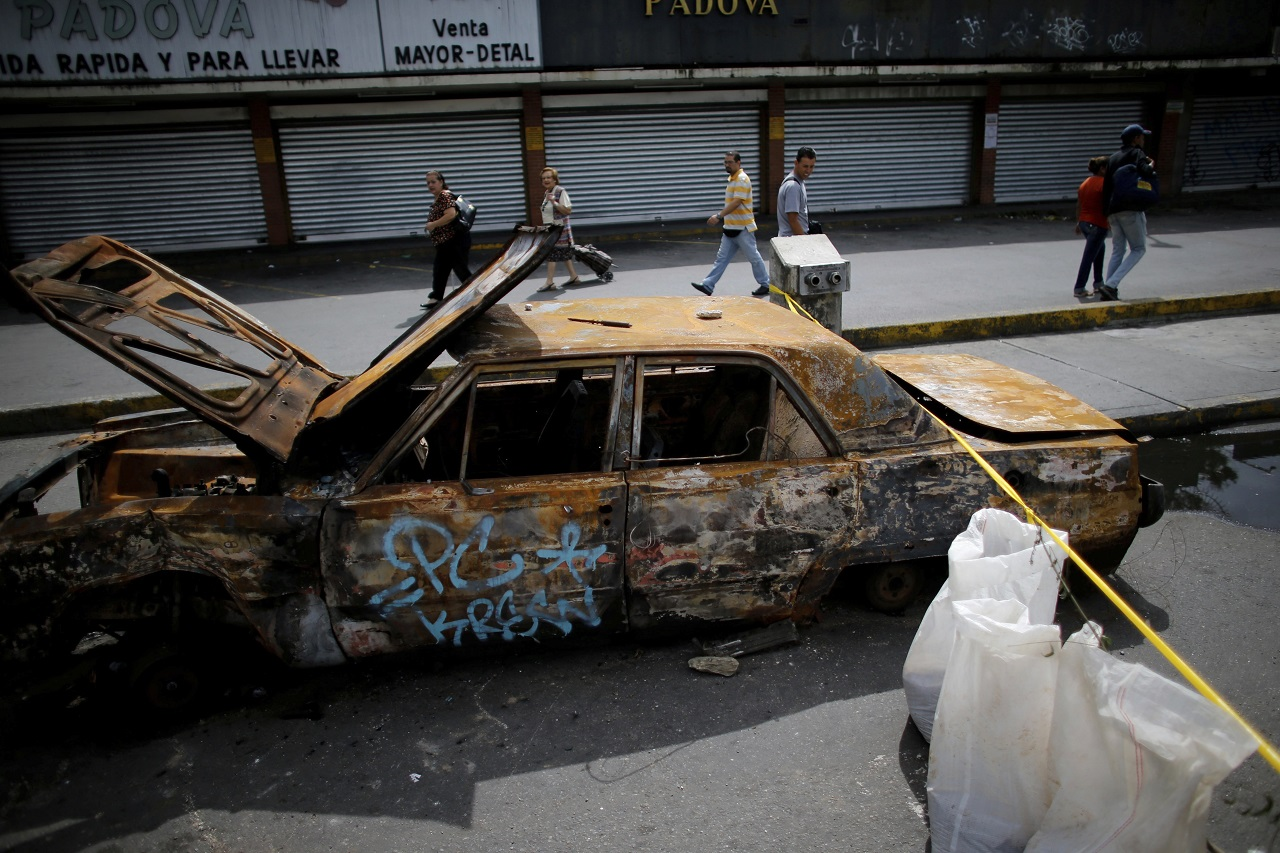 Pedestrians walk past closed shops and a barricade set up by demonstrators on the second day of a 48-hour general strike in protest of government plans to rewrite the constitution, in Caracas, Venezuela, Thursday, July 27, 2017.
