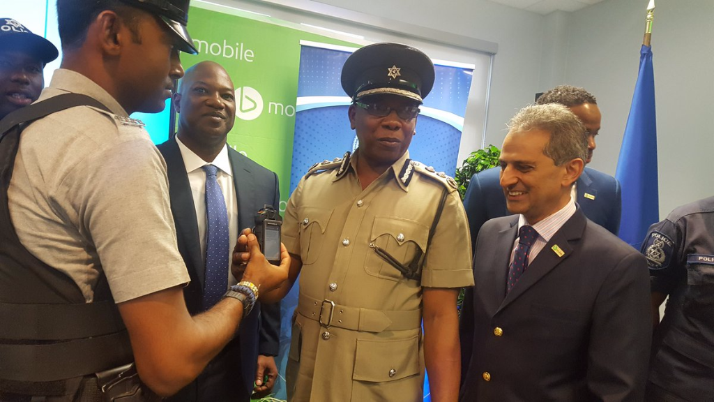 Acting Police Commissioner Stephen Williams (2nd from right)demonstrates camera to be used by police officers in national Body Worn Camera Pilot Project.