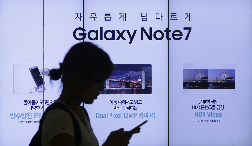 In this Sept. 2, 2016, file photo, a woman walks by an advertisement of Samsung Electronics' Galaxy Note 7 smartphone at the company's showroom in Seoul, South Korea.  (AP Photo/Ahn Young-joon, File)
