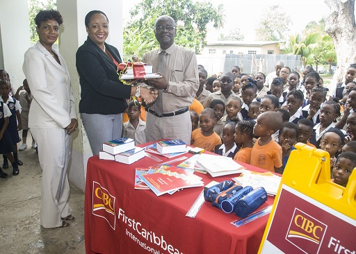 Principal of Eagle Hall Primary School, Mr. Orlando Jones, right, accepting the gifts of books and supplies from CIBC FirstCaribbean International Bank's Director of Operational Risk, Khadija Bourne. Mrs. Kelvine Jordan-Rowe is at left.
