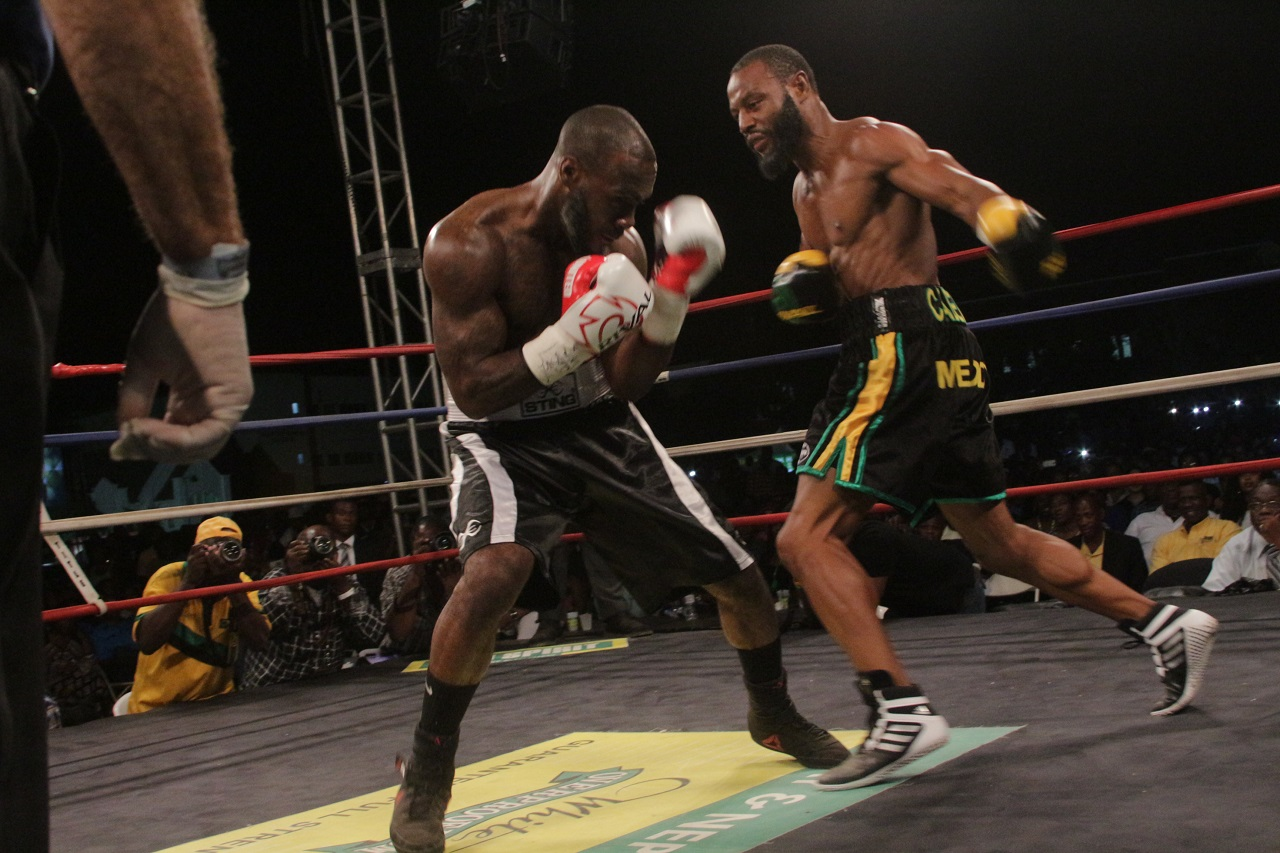 Jamaican Sakima Mullings (right) moves in to attack Canadian Phil Rose during the final of the Contender Boxing Series on Wednesday night at Mico University.