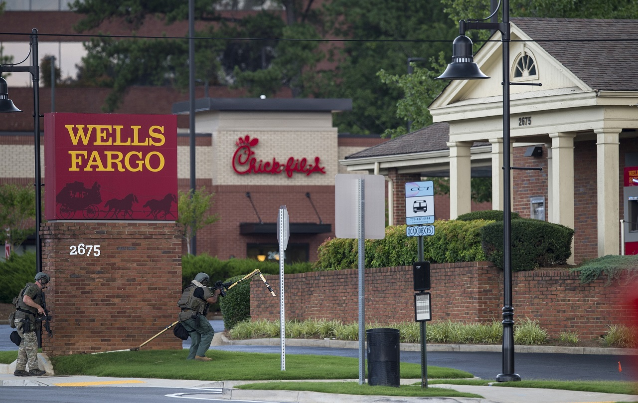 """Police officers move toward a Wells Fargo Bank, Friday, July 7, 2017 in Marietta, Ga. A man who claimed to have a bomb that could """"take out the room"""" barricaded himself inside a suburban Atlanta bank Friday, sparking an hours-long standoff that forced police to bust through a brick wall of the building and later ended with the suspect's death."""