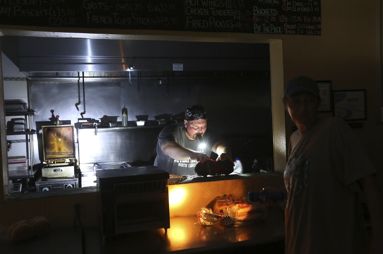 Aaron Howe cooks in the dark kitchen at the Island Convenience Store in Rodanthe on Hatteras Island, N.C., on Friday, July 28, 2017 after a widespread power outage.