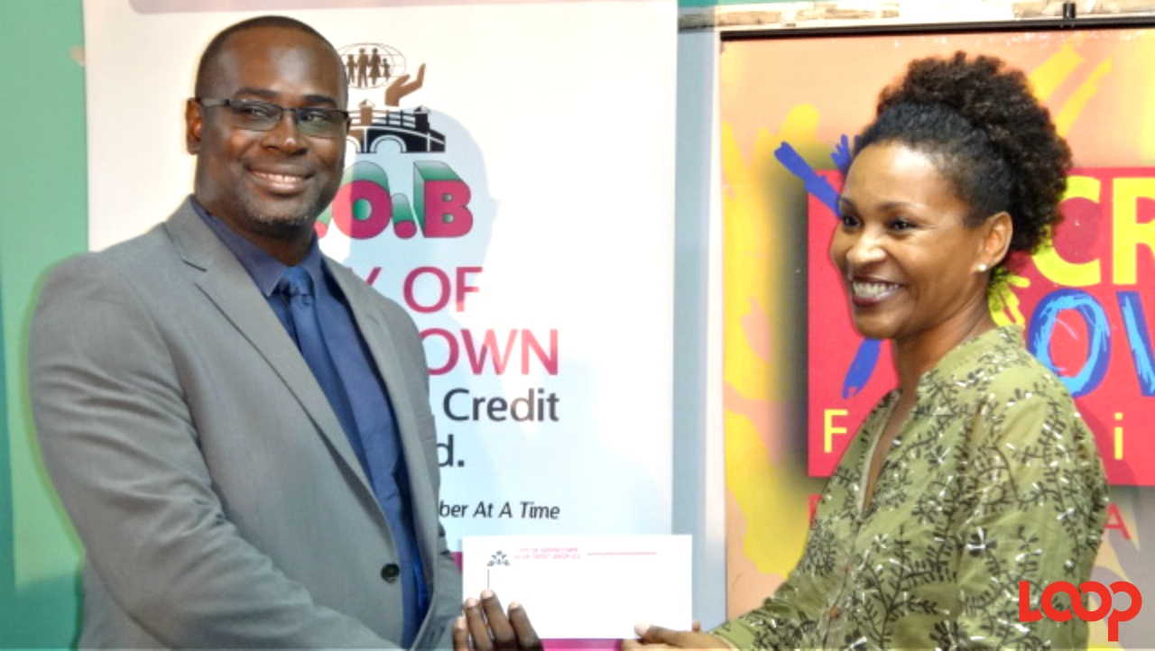 COP President, Henderson Williams, presents a cheque to Amanda Cumberbatch of the NCF.