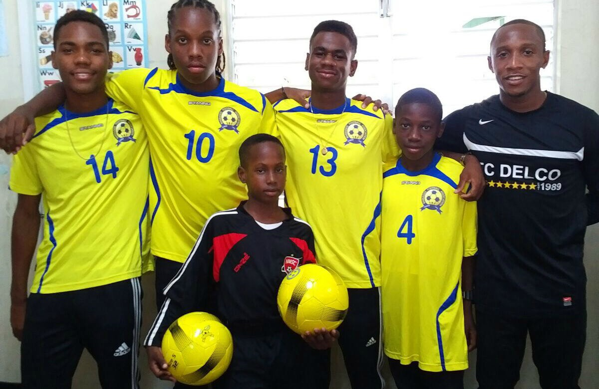 Members of the U15 football team and (right) Coach Renaldo Gilkes.
