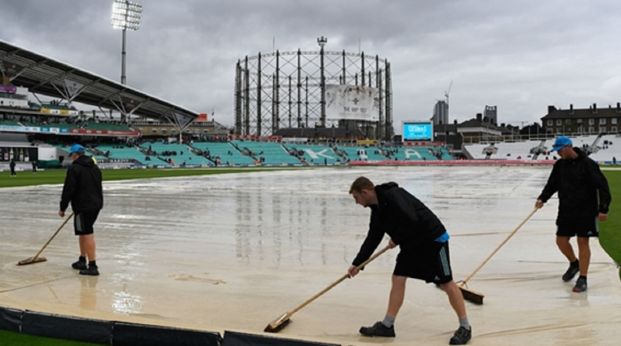 The groundstaff at The Oval clear away water.