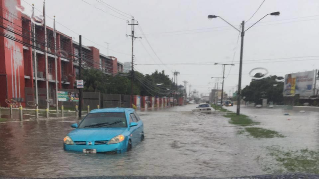 Photo: A car is partially submerged as the driver tries to navigate heavy flood water along Wrightson Road, Port of Spain, on Sunday July 2, 2017.