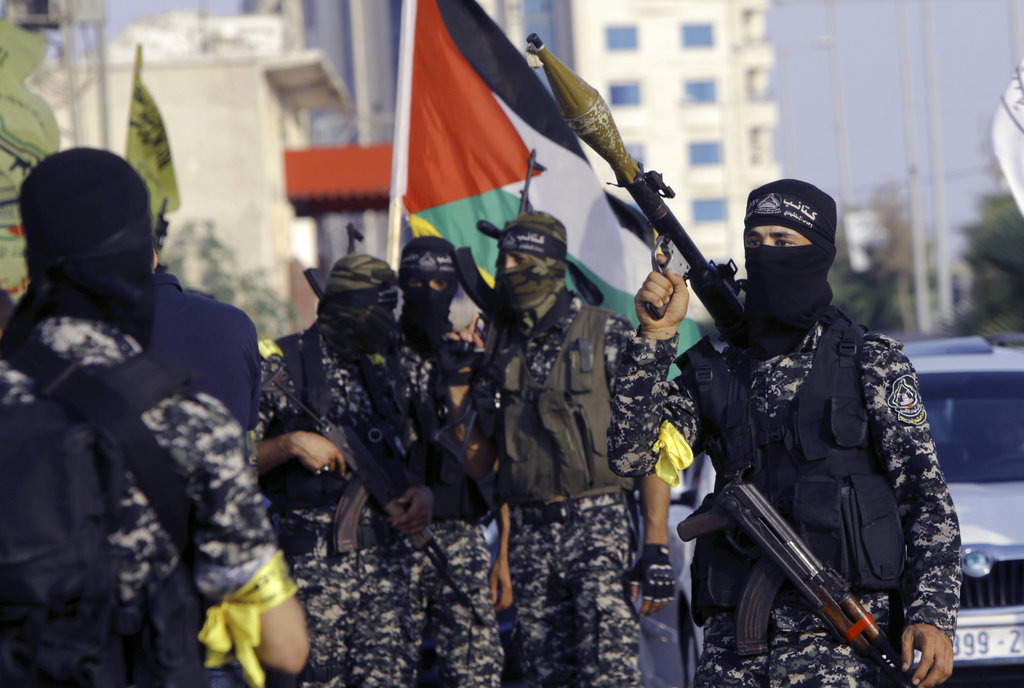 Masked militants from Nabil Masoud Brigades, a military wing of the Fatah movement, hold their weapons during a parade against Israeli arrangements in a contested Jerusalem shrine, along the streets of Gaza City, Tuesday, July 25, 2017. (AP Photo/Adel Hana)
