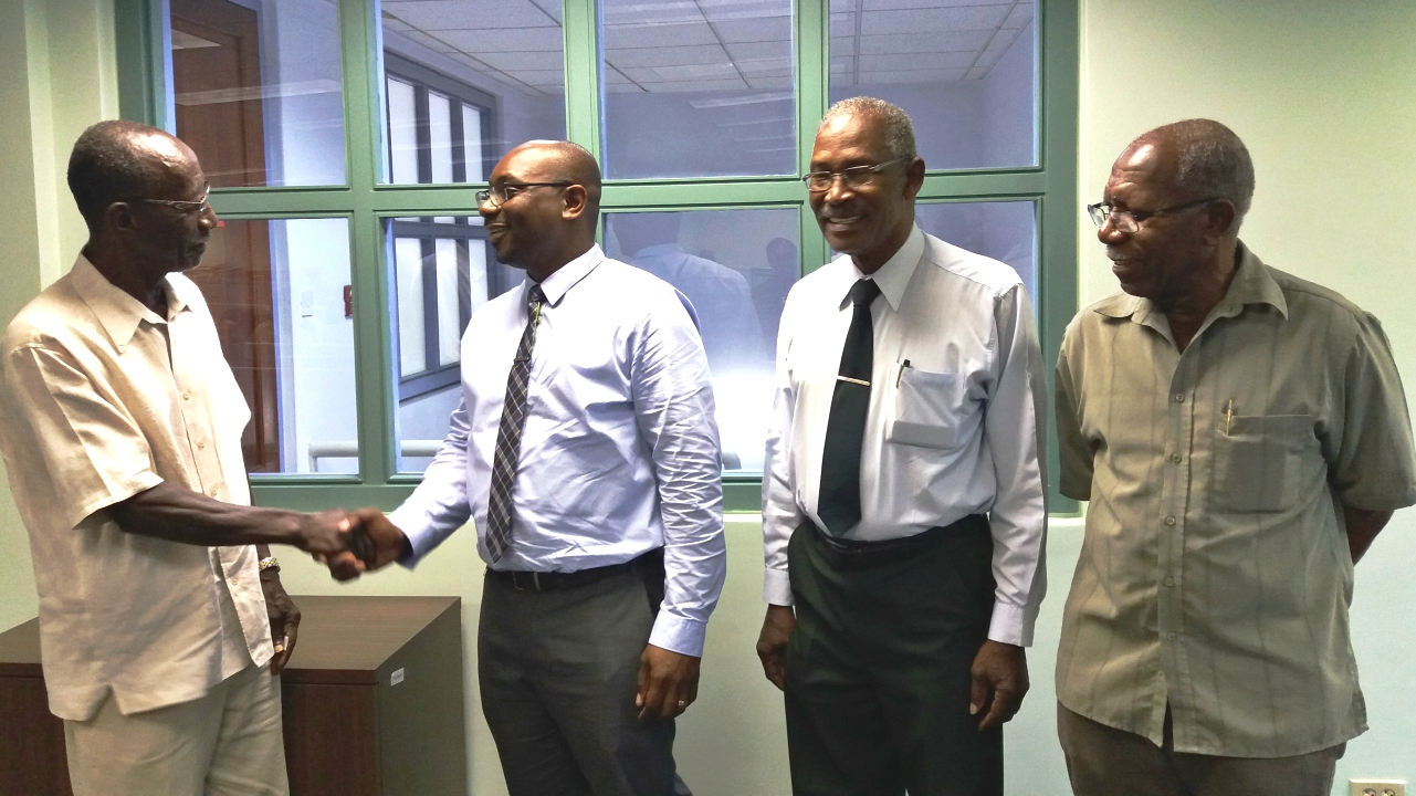 The FSC's newly appointed CEO, Kester Guy (second left) is being congratulated by FSC Chairman, Sir Frank Alleyne. Looking on are fellow Board commissioners Lawson Yearwood (second right) and Basil Murray (right).