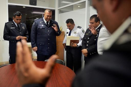 """Des membres de la """"police céleste"""" prient dans les bureaux de la police municipale à Tlanepantla de baz, le 26 juin 2017 au Mexique"""