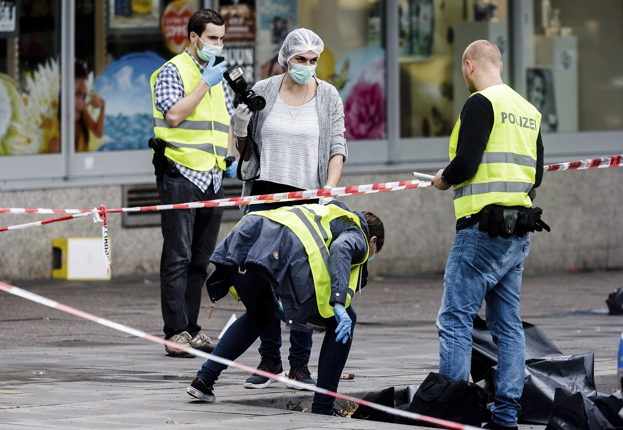 Police officers are securing evidence in front of the supermarket in Hamburg, Germany, Friday, July 28, 2017, where a man with a knife fatally stabbed one person and wounded four others as he fled, police said. He was then arrested.