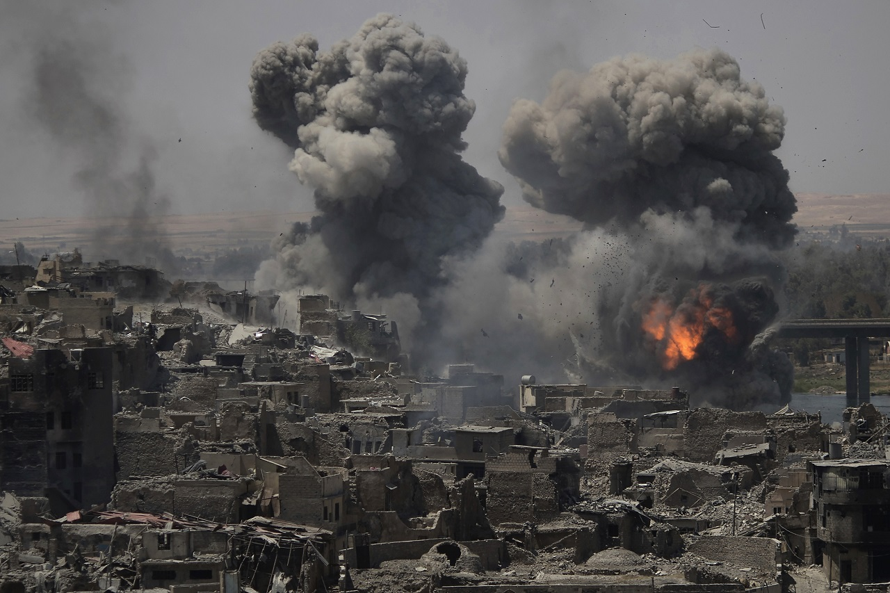 Smoke billows from Islamic State positions on the edge of the Old City a day after Iraq's prime minister declared