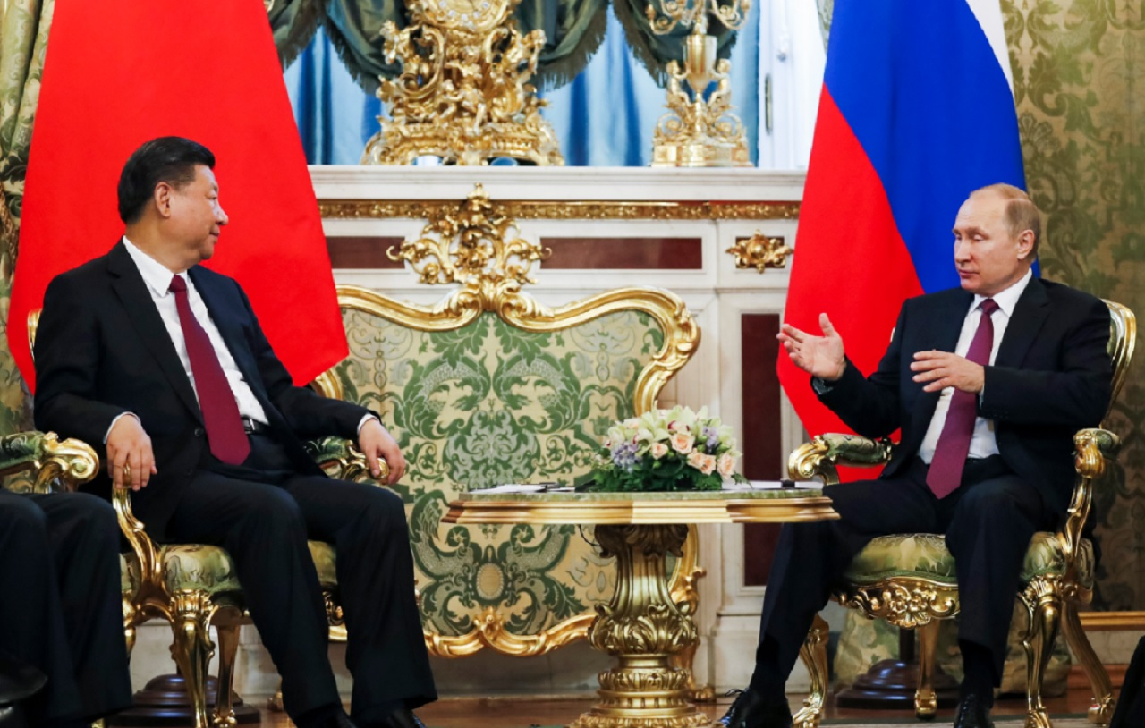 Vladimir Putin, right, speaks with Chinese President Xi Jinping.