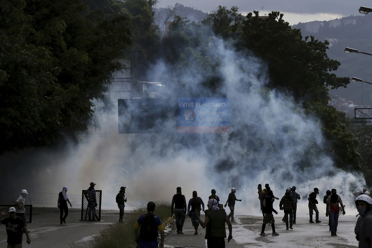Demonstrators walk amid tear gas fired by Bolivarian National Guards during clashes in the El Hatillo neighbourhood on the outskirts of Caracas, Venezuela, Thursday, July 20, 2017.